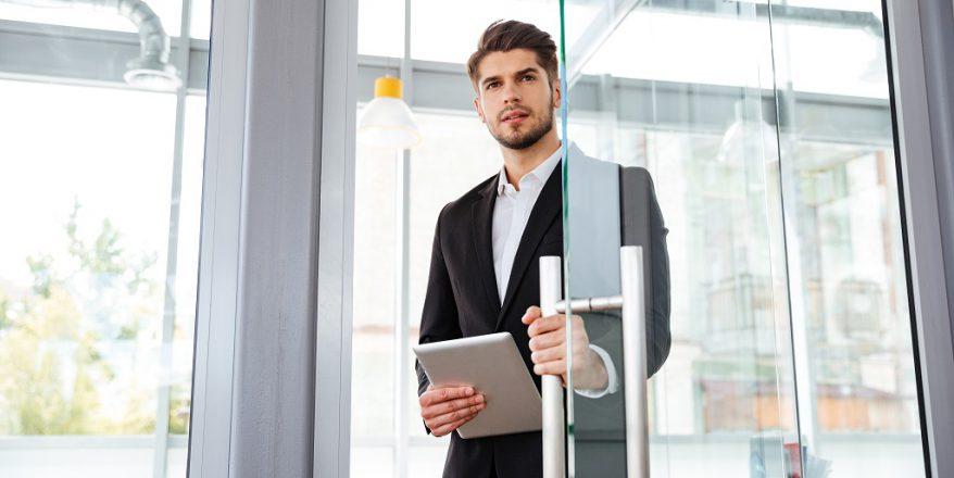 Executivo abrindo uma porta após usar um sistema de Segurança Biométrica